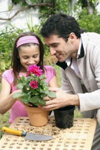 Father and daughter plant a flower.